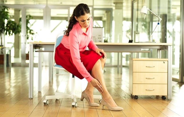 Femeie așezată la birou, atingându-și piciorul obosit