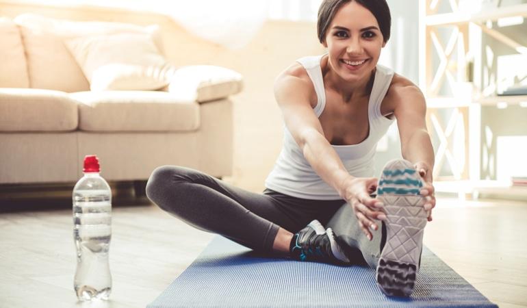 Femeie pe un covoraș de yoga,care se apleacă pentru a-și  întinde ambele picioare pentru a preveni insuficiența venoasă