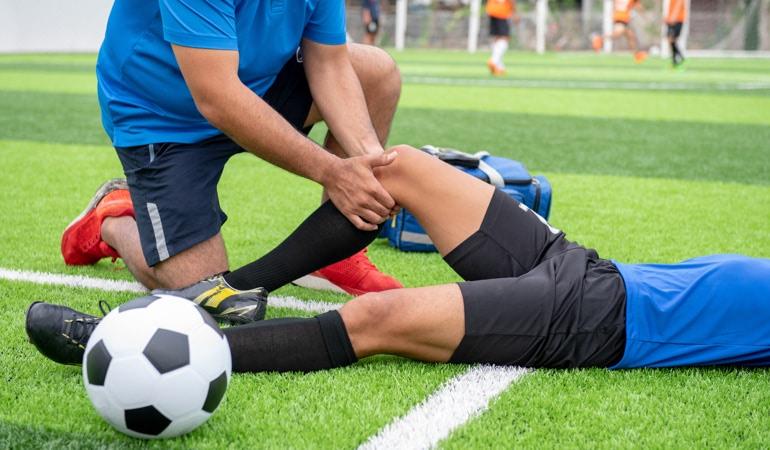 Un jucător de fotbal accidentat și un medic cu Lioton®  1000Gel