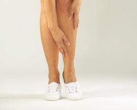 Женщина втирающая не оставляющий пятен Лиотон 1000® гель в усталые икроножные мышцы