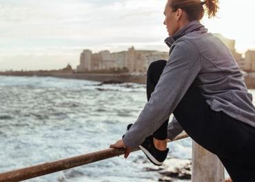 Женщина наклоняется вперед, чтобы размять уставшие ноги после пробежки по городу в целях предотвращения венозной недостаточности