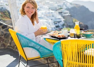 Энергичная улыбающаяся женщина, наслаждающаяся здоровым завтраком, чтобы предотвратить венозную недостаточность
