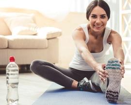 Женщина выполняет гимнастику для вен на коврике для йоги, чтобы предотвратить тяжесть в ногах