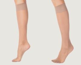 Женские ноги в поддерживающих чулках для профилактики венозной недостаточности