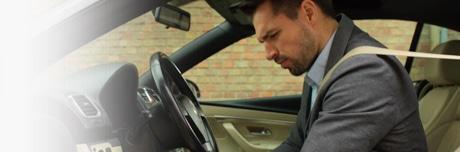 Мужчина с тяжестью в ногах сидит в машине